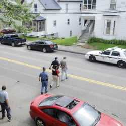 An Augusta police detective and other law enforcement personnel escort a man arrested on outstanding warrants to a waiting cruiser Thursday on Northern Avenue. State and county law enforcement officers accompanied Augusta police on walks through several neighborhoods in the city.