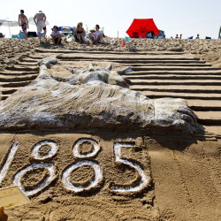 "Peter Wilson, 58, of Montreal writes ""1885"" at the base of his team's sand sculpture of the Statue of Liberty during the 29th annual Family Sand Sculpture Competition in Ocean Park on Friday. Wilson's family has been vacationing in Ocean Park for 86 years and has taken part in the sculpture competition for many years.  Gabe Souza/Staff Photographer"