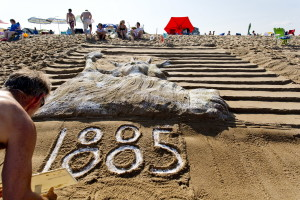 """Peter Wilson, 58, of Montreal writes """"1885"""" at the base of his team's sand sculpture of the Statue of Liberty during the 29th annual Family Sand Sculpture Competition in Ocean Park on Friday. Wilson's family has been vacationing in Ocean Park for 86 years and has taken part in the sculpture competition for many years.  Gabe Souza/Staff Photographer"""