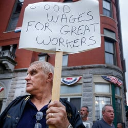 Brian Bubier of Sanford pickets in support of his stepson, who is a Biddeford police officer, in front of Biddeford City Hall on Tuesday evening. Union members from the police and public works departments picketed at City Hall and converged on the City Council meeting.  Derek Davis/Staff Photographer