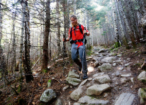 """James Lunning of Minneapolis, who goes by the trail name of """"Attrition,"""" hikes down Hunt Trail after summiting Mount Katahdin in the dark and watching the sun rise. Lenning hiked the entirety of the Appalachian Trail."""