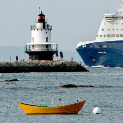 The Nova Star ferry dwarfs fishermen and tourists as it passes by Spring Point Ledge Light on its way to the Ocean Gateway terminal.