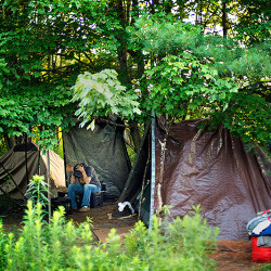 Terry Walters sits in a homeless encampment in a wooded area on the outskirts of Portland in July. A new federal report says the number of homeless Mainers declined in 2015, but the state has twice as many unsheltered homeless people as it did in 2010.