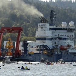 The Royal Dutch Shell PLC icebreaker Fennica heads up the Willamette River as protesters in kayaks chase after it in Portland, Ore., Thursday, July 30, 2015. (AP Photo/Don Ryan)
