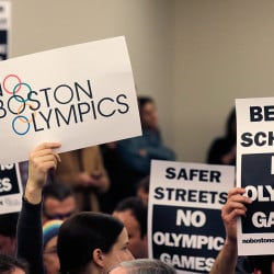 People hold up placards against the Olympic Games coming to Boston during  a public forum in February in Boston.