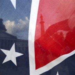 The South Carolina State House is seen through a Confederate flag held along Gervais Street on Monday in Columbia, S.C. Gerry Melendez/The State via AP