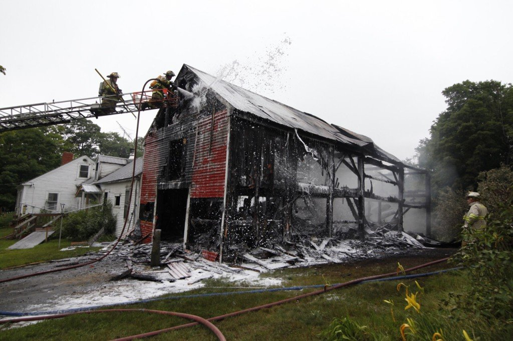 Firefighters douse a barn fire at 3000 Milton Mills Road in Acton. Jill Brady/Staff Photographer