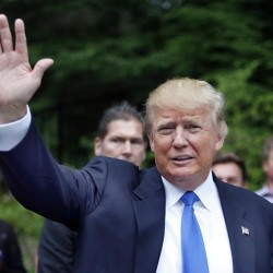 In this June 30, 2015, photo, Republican presidential candidate Donald Trump waves as he arrives at a house party in Bedford, N.H. Hispanic leaders are warning of harm to Republican White House hopes unless the party's presidential contenders do more to condemn Trump, who's refusing to apologize for calling Mexican immigrants rapists and drug dealers.  (AP Photo/Jim Cole)
