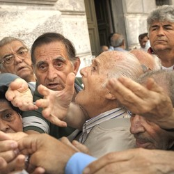 Pensioners try to get a number to enter a bank in Athens Wednesday. About 1,000 bank branches around the country were ordered by the government to reopen  to help desperate pensioners without ATM cards withdraw cash up to 120 euros ($134) from their retirement checks. The Associated Press