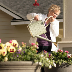 Amy Shives waters her flowers at her house in Spokane, Wash. Shives was diagnosed with early-onset Alzheimer's disease in 2011. Nearly two-thirds of Americans with Alzheimer's disease are women, and now some scientists are questioning the long-held assumption that it's just because women tend to live longer than men.