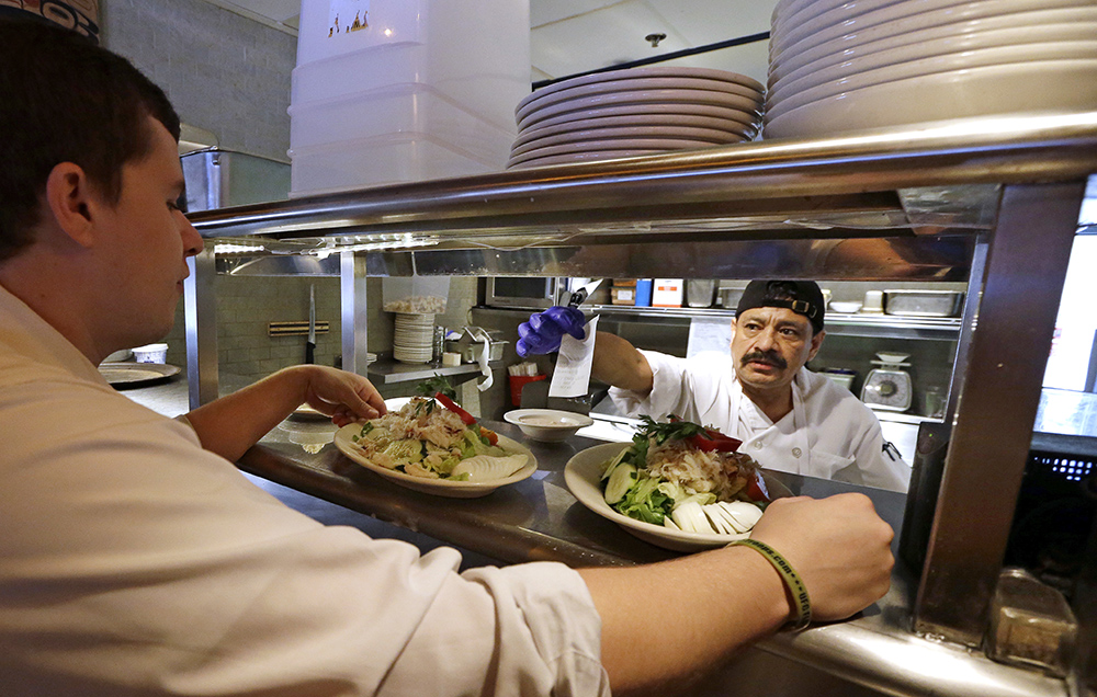 Cook Bulmaro Sosa  goes over a food order with server Zachary DeYoung at an Ivar's restaurant in Seattle. The Associated Press