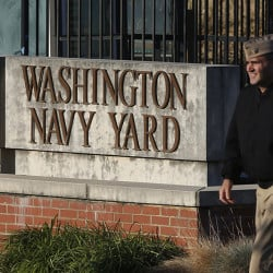 FILE - In this Sept. 19, 2013 file photo. military personnel walks past an entrance to the Washington Navy Yard in Washington. An official says shots have been reported in a building on the Washington Navy Yard campus.   (AP Photo/Charles Dharapak, File)