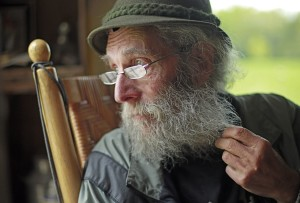 Burt Shavitz pauses during a May 23, 2014,  interview to watch a litter of fox kits play near his camp in Parkman, Maine. Robert F. Bukaty/The Associated Press