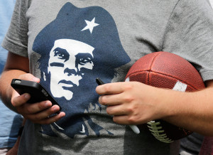 A Patriots fan, wearing a Che Guevara-like T-shirt depicting quarterback Tom Brady, waits for a chance to get an autograph Thursday in Foxborough.
