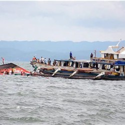 The Philippine Coast Guard rescues boat passengers after a ferry capsized in choppy waters Thursday in Ornoc, Philippines. The Ferry had just departed the port of Ornoc on Leyte heading to Camotes islands when it was capsized by large waves, the coast guard said. The Associated Press