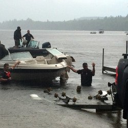 The Maine Warden Service removes one of the boats damaged in Thursday's crash out of Thompson Lake at the public boat launch in Otisfield.