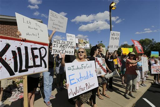Protesters gather outside Dr. Walter James Palmer's dental office in Bloomington, Minn., Wednesday. The Associated Press