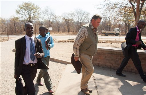 Theodro Bronkhorst, center, a professional hunter, arrives at the magistrates courts in Hwange, Zimbabwe, Wednesday. Bronkhorst has been charged with  failure to prevent an unlawful hunt that resulted in the killing of Cecil the lion by Minnesota dentist, Walter James Palmer. The Associated Press