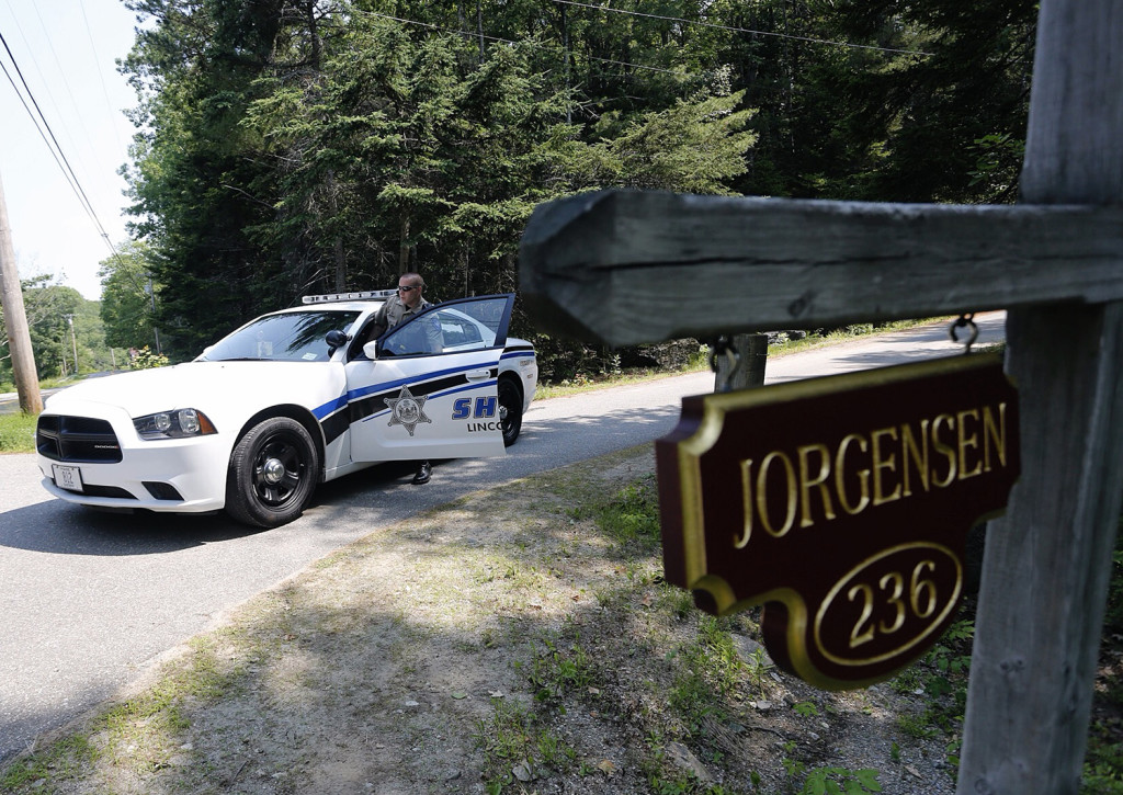 Deputy Chubbuck of the Lincoln County Sheriff's Department stands by the entrance to the Jorgensen residence on Lakeside Drive. Derek Davis/Staff Photographer