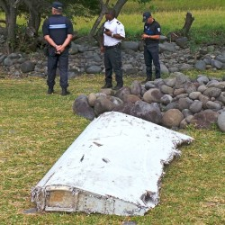 Gendarmes and police stand near a large piece of plane debris that was found on the beach in Saint-Andre, on the French Indian Ocean island of La Reunion, Wednesday. Reuters