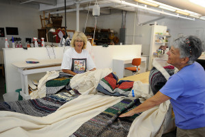 """Jo Israelson, left, examines the fabric tent that will be part of the """"Welcoming the Stranger"""" exhibit at the Maine Jewish Museum. Helping her is Melodi Hackett, right, who arranged the sewing of all the woven sections and muslin to make the massive tent."""
