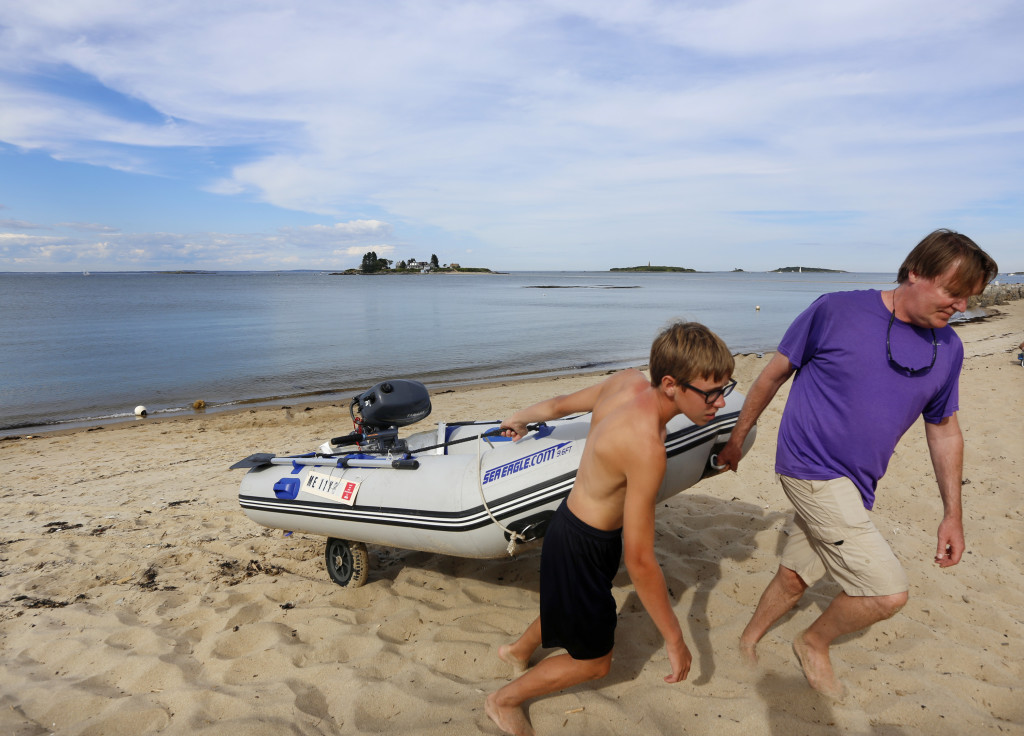 Keith McManus of Barrington, R.I., drags his inflatable boat up from the water with the help of his son Kieran, 13, after helping to rescue two men who had become stranded by the incoming tide between Hills Beach and Basket Island in Biddeford. Derek Davis/Staff Photographer