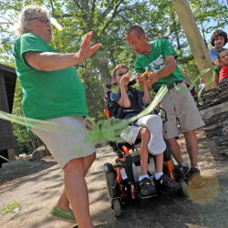 Nicholas Alexander, center, cuts a ceremonial ribbon Tuesday with Dawn Willard-Robinson, left, and Harvey Chesley, right, for the dedication of a handicapped-accessible playground at Pine Tree Camp in Rome.
