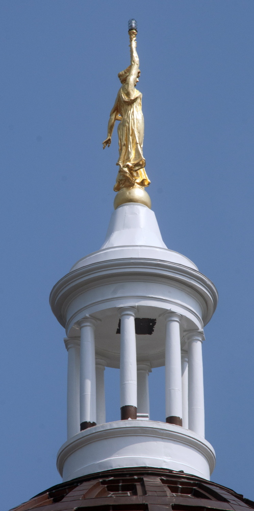 Peeling paint on the pillars around the State House dome in Augusta can be seen Wednesday.