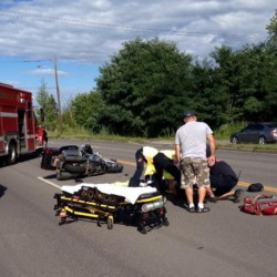 Emergency responders help a motorcyclist who was injured in a collision with a Jeep on College Avenue Thursday afternoon in Waterville.