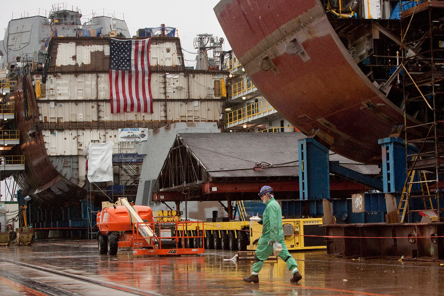 A shipbuilder walks in the yard, with partial ship assemblies behind him, at Bath Iron Works in Bath