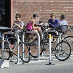 Patrons chat at tables next to a bike rack outside Arabica Coffee and Rosemont Market & Bakery on Commercial Street in Portland.