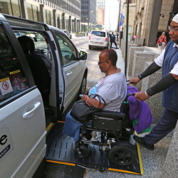 Driver Carl James helps Renita Freeman into his van as she leaves her job at the Ralph Metcalfe Federal Building in Chicago.
