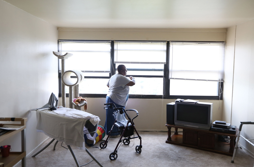 """Renita Freeman opens a window in her Chicago apartment. She can walk in short bursts but needs a wheelchair when she leaves her building. """"I'm not a stay-in-the-house kind of girl,"""" Freeman said. """"I like to get out, smell the roses."""""""