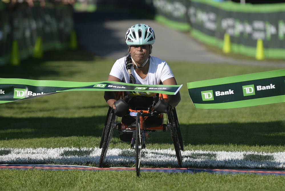 Christina Kouros of Cape Elizabeth is the first female in the wheelchair category to cross the finish line of Saturday's TD Beach to Beacon.