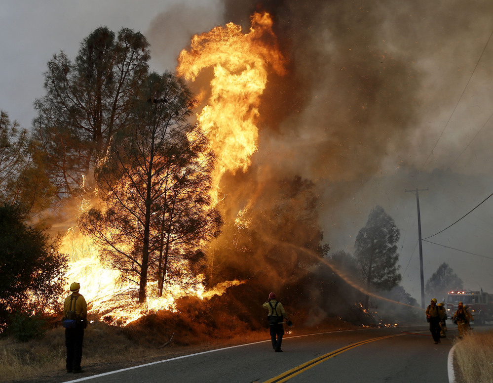 Firefighters spray water at a fire along Morgan Valley Road near Lower Lake, Calif., on Friday. Wildfires in Northern California were intensified by dry vegetation, triple-digit temperatures and gusting winds.