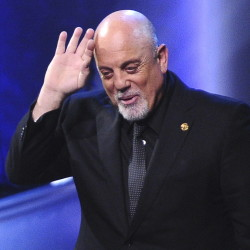 New York officials debate whether the Piano Man should get a road named for him while he's still alive.