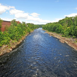 A section of the Kennebec River flows under the footbridge below the Weston Dam, where a railroad trestle used to be. The railroad bridge wreckage must be removed before a whitewater park planned for the river can be built.