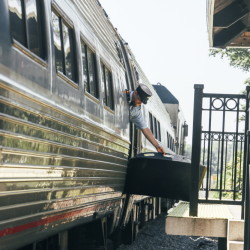 An Amtrak employee lowers the ramp of the Downeaster to the platform of the Old Orchard Beach station last Tuesday. The Northern New England Passenger Rail Authority, which operates the Downeaster,  has hopes of re-earning passengers' trust after 16 months of stunning unreliability.