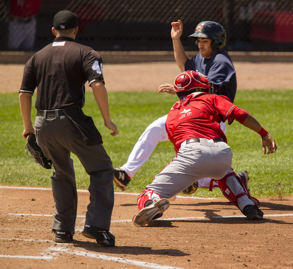 Carlos Asuaje of the Sea Dogs slides around the attempted tag by Harrisburg Senators catcher Pedro Severino to score a run Sunday during Portland's 16-12 loss.
