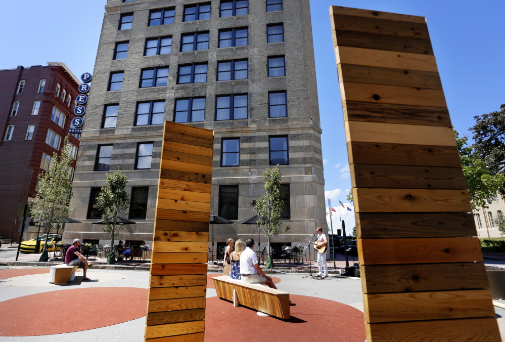 Local musician Pete Miller performs Saturday at the Federal Street Folly, a pop-up park in Portland sponsored by the Press Hotel, in background. A hotel official said the park is an effort to make upper Exchange Street and the downtown more pedestrian-friendly.