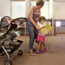 Isabel Alves, 4, looks at the ballot for the Scarborough school budget vote after her mother, Laurie Alves, voted at the Scarborough Municipal Building on Tuesday. It was the third time Alves voted for the school budget, which she wanted to see approved so no school programs would get cut. Sleeping in the stroller at left is 3-month-old Lillian Alves.