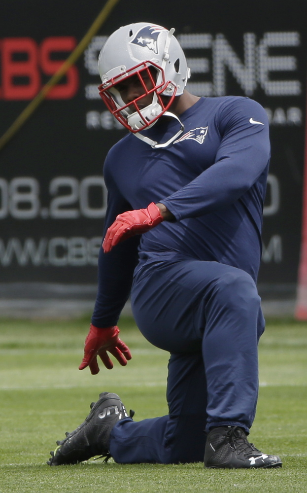 Patriots defensive lineman Dominique Easley stretches during an NFL football minicamp in June.
