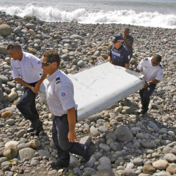 In this July 29, 2015 file photo, French police officers carry a piece of debris from a plane in Saint-Andre, Reunion Island.