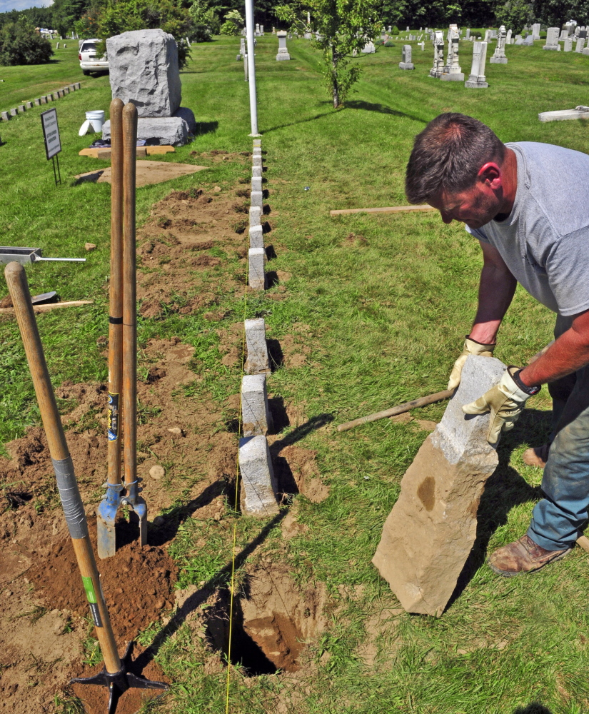 Kevin Miller replaces one of a row of 4-by-4-inch granite markers Wednesday in one of the soldiers' lots at Mount Pleasant Cemetery in Augusta.