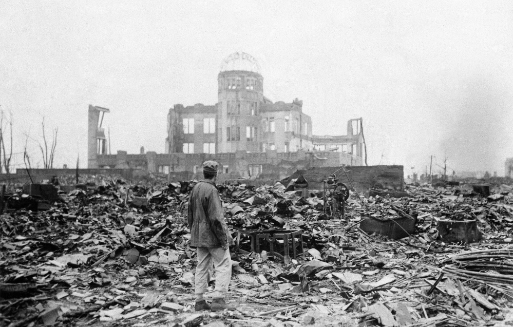 On Sept. 8, 1945, an allied correspondent stands in the rubble of Hiroshima, Japan. The building in the backgound is preserved as the Atomic Bomb Dome. Hiroshima was bombed on Aug. 6, 1945. Nagasaki was bombed three days later.