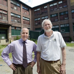 Alan Manoian, left, economic development specialist in Auburn, and Roland Miller, director of planning and development, on Thursday stand in front of the dilapidated shoe factory on Minot Avenue in Auburn that Chinese investors announced they plan to convert into a health and wellness hotel aligned with Central Maine Medical Center in Lewiston.