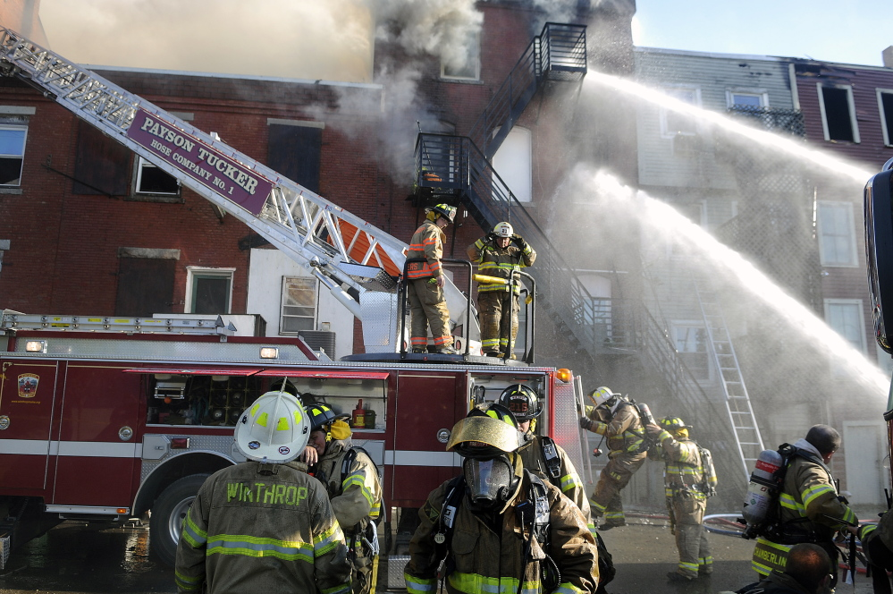 Firefighters on July 16 apply water to one of the buildings on Water Street in Gardiner that sustained extensive fire damage.