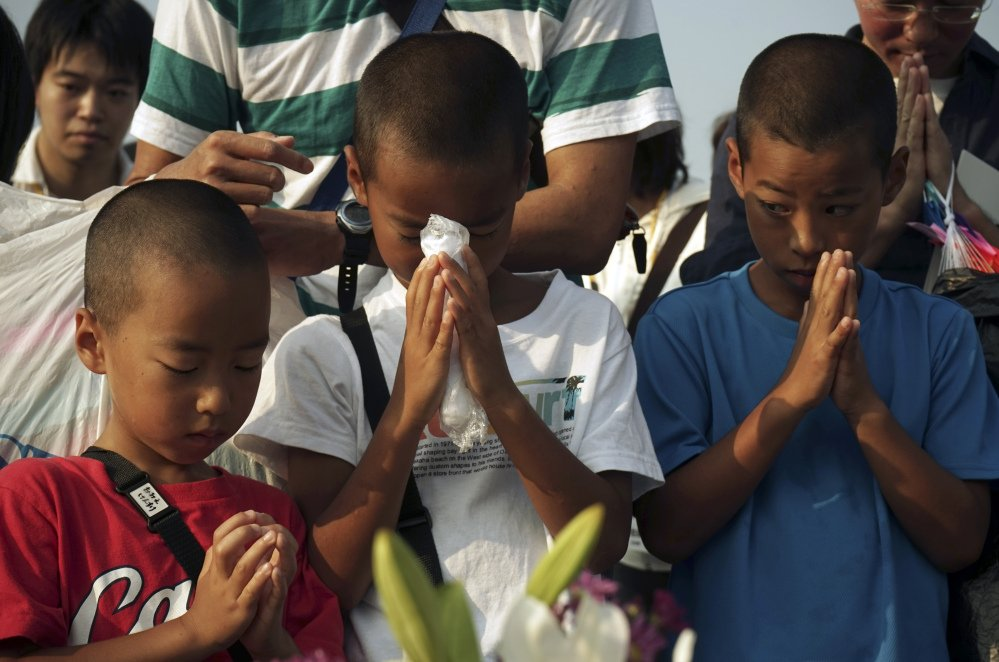 Children pray for the atomic bomb victims in front of the cenotaph at the Hiroshima Peace Memorial Park in Hiroshima, Japan, early Thursday as Japan marked the 70th anniversary of the atomic bombing of Hiroshima.