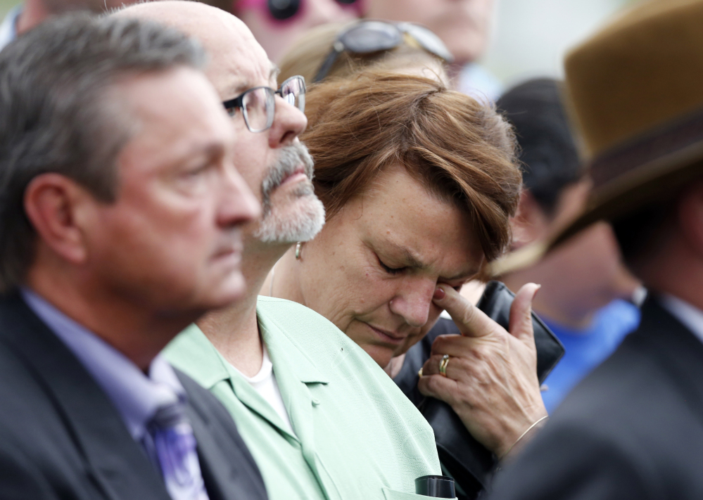 A woman who accompanied Tom Sullivan, who lost his son, Alex, in the theater shootings, wipes tears outside the Arapahoe County Courthouse after hearing the jury's decision.