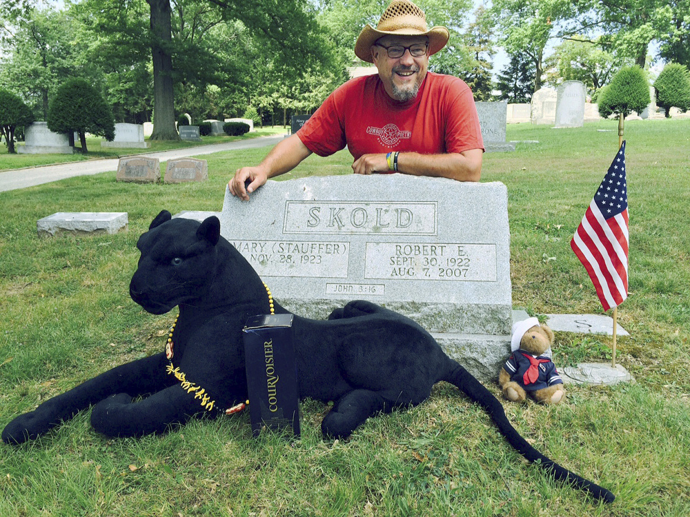 Walter Skold of Freeport poses Friday at the grave of his father in York, Pa. The Dead Poets Society of America founder visited his father's grave after completing his summer tour of 97 poets' graves in 70 days. With Skold is his mascot Raven, a stuffed black panther that was given to him.